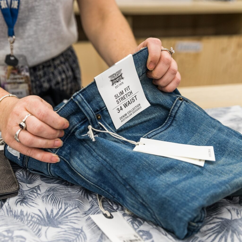 person in blue denim jeans holding white paper